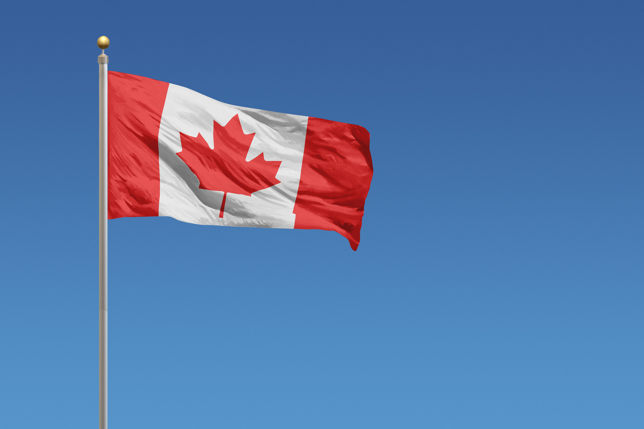Flag of Canada in front of a clear blue sky